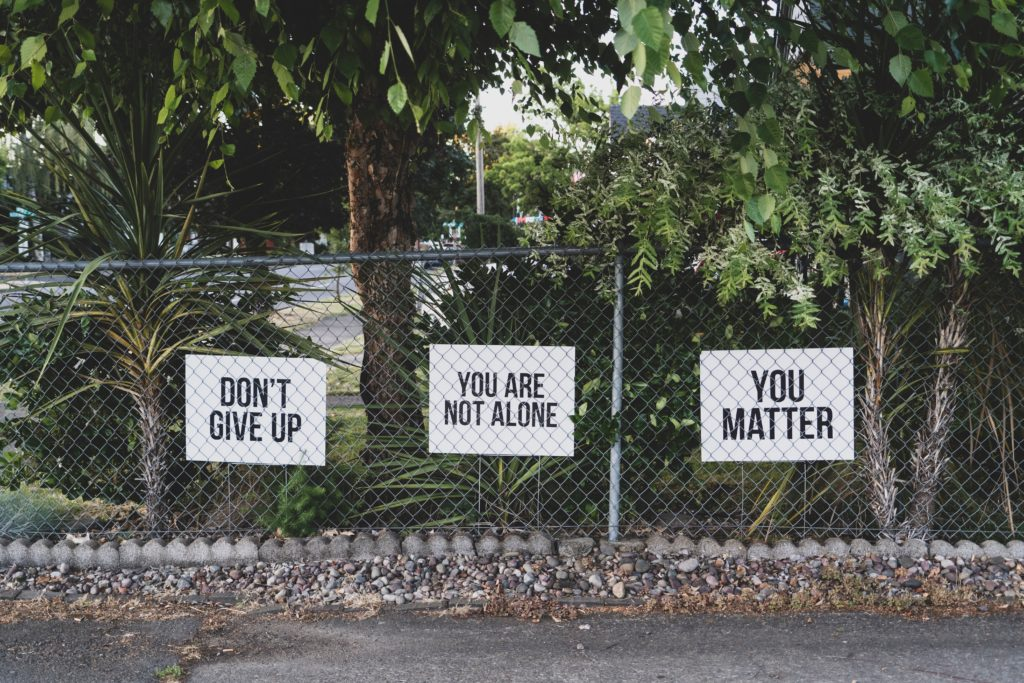 mental health signs- don't give up, you are not alone and you matter signs on a fence.